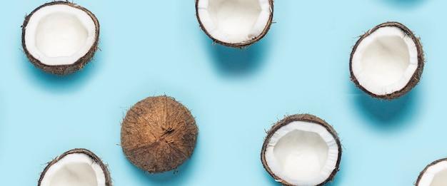 Molte metà aperte della noce di cocco e una foglia di una palma su una priorità bassa blu