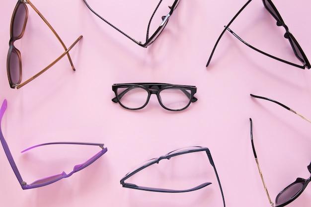 Molte paia di occhiali su sfondo rosa