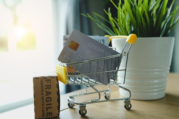 Molti soldi in scatola di carta e carte di credito nello shopping