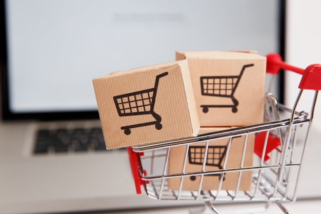 Molte scatole di carta in un piccolo carrello sulla tastiera di un laptop concetti sullo shopping online che i consumatori possono acquistare direttamente da casa o dall'ufficio con pochi clic tramite il browser web