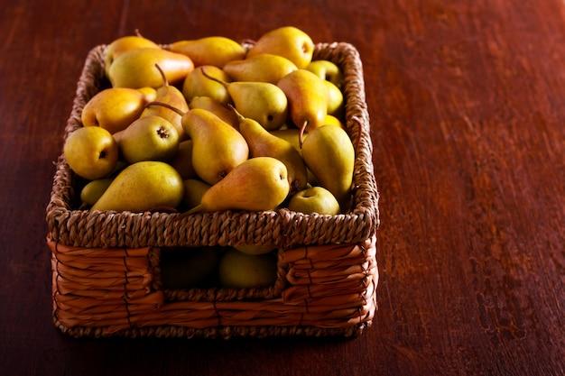Molte pere in un cesto sul tavolo marrone
