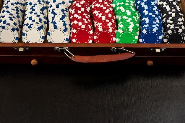 Molte fiches da poker in una valigia isolata su uno sfondo nero. poker