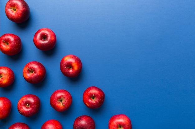 Molte mele rosse su sfondo colorato, vista dall'alto. modello autunnale con mela fresca sopra vista con copia spazio per disegno o testo.