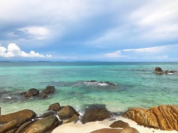 Molte rocce sulla spiaggia sabbiosa sullo sfondo del cielo e del mare in una giornata di sole.