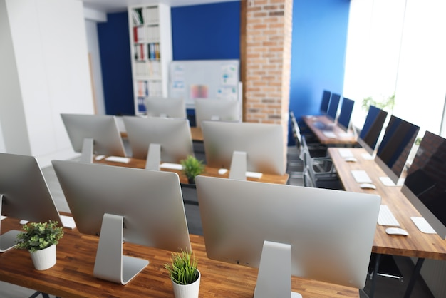 Molti monitor d'argento stanno su un tavolo di legno in primo piano dell'ufficio. programmatore concetto di formazione professionale
