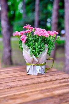 Molti piccoli chiodi di garofano rosa in vaso sul tavolo di legno all'aperto.