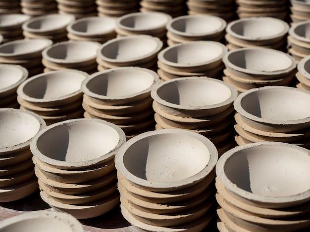 Tanti piccoli piatti, di forma rotonda realizzati con argilla ceramica ed essiccati al sole. fabbricazione del processo di terracotta.