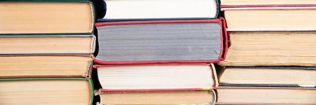 Molte pile di libri. vecchi libri con copertina rigida come sfondo. di nuovo a scuola.