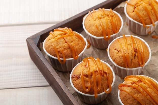 Molti muffin gustosi dolci sulla tavola di legno