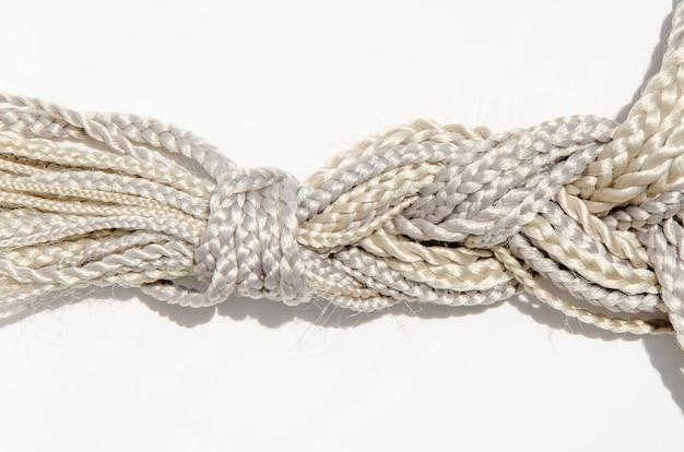 Tante trecce in fibra sintetica con armature diverse, raccolte in un'unica treccia. materiale kanekalon