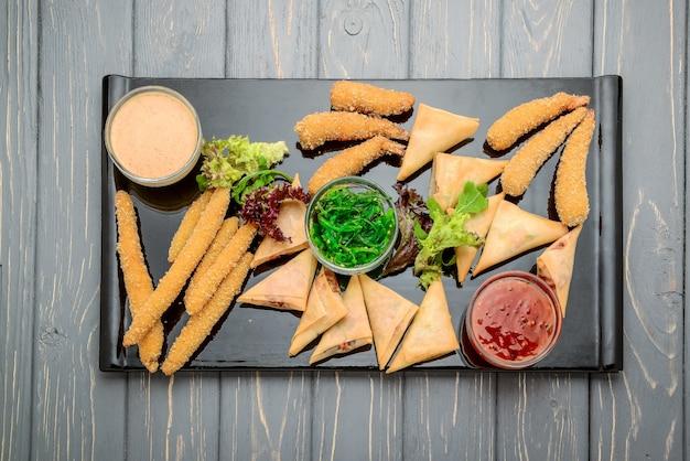 Molti tipi di snack salati con diverse salse e insalate