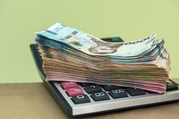 Molti soldi dell'ucraina che si trovano sulla calcolatrice 1000 banconote. uah
