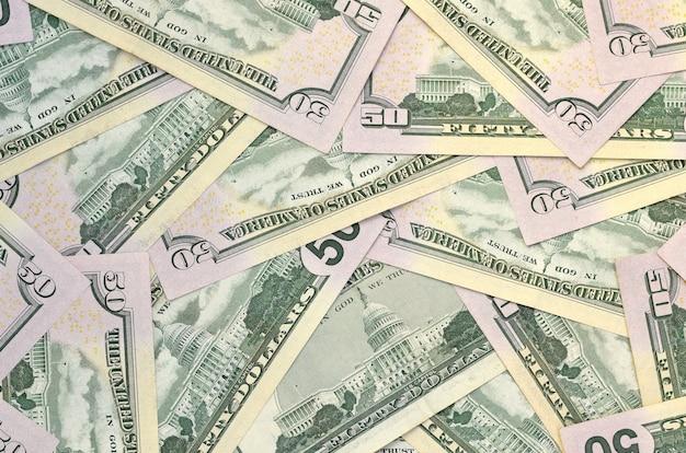 Molte banconote in dollari degli stati uniti cinquanta sulla fine piana della superficie del fondo su. vista dall'alto piatta. concetto astratto di affari