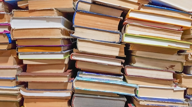 Molti usavano vecchi libri nella biblioteca della scuola. disposizione caotica di pile di letteratura, messa a fuoco selettiva. una pila di libri termina con uno sfondo impilato. libri in una biblioteca - sfondo.