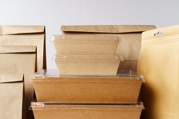 Molti vari contenitori per alimenti da asporto, scatole per pizza, tazze da caffè e sacchetti di carta su sfondo grigio chiaro. consegna del cibo