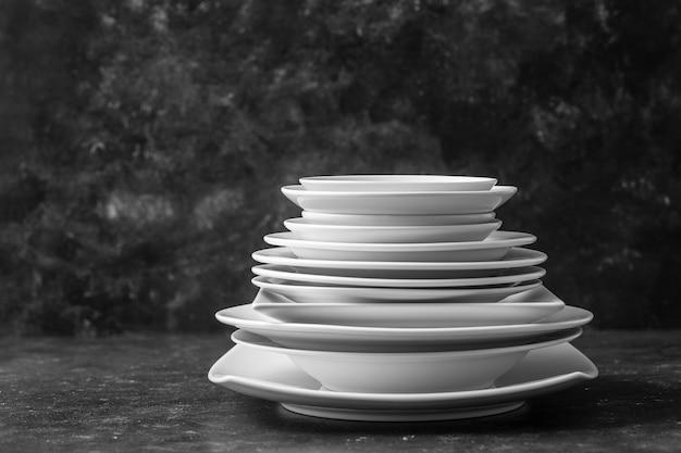 Molti piatti di ceramica vuoti bianchi su sfondo nero, primi piani. piatti bianchi impilati su sfondo scuro