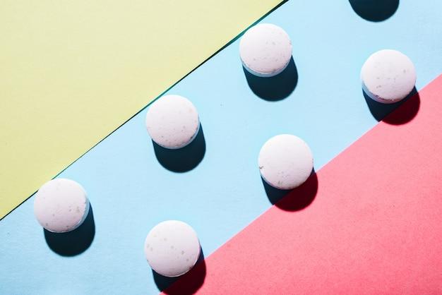 Molte pillole mediche bianche in fila su uno sfondo rosa e blu e giallo