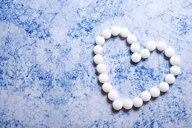 Molte pillole bianche dal cuore su sfondo blu. accettare il concetto di doni. cardiologia o concetto di amore
