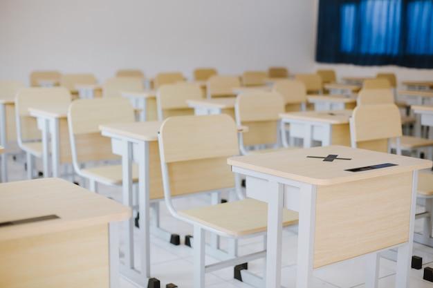 Molti tavoli e sedie in legno ben disposti in un'aula vuota