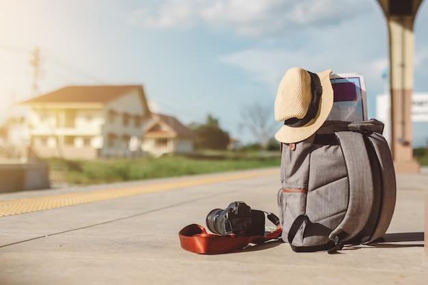 Mappa in zaino, telefono cellulare con auricolare e cappello alla stazione ferroviaria con un set traveller.sun, concetto di viaggio.