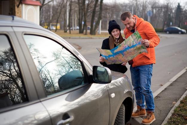 Mappa nelle mani dei giovani sulla strada con una macchina.