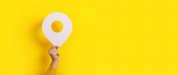 Puntatore della mappa 3d pin in mano su giallo