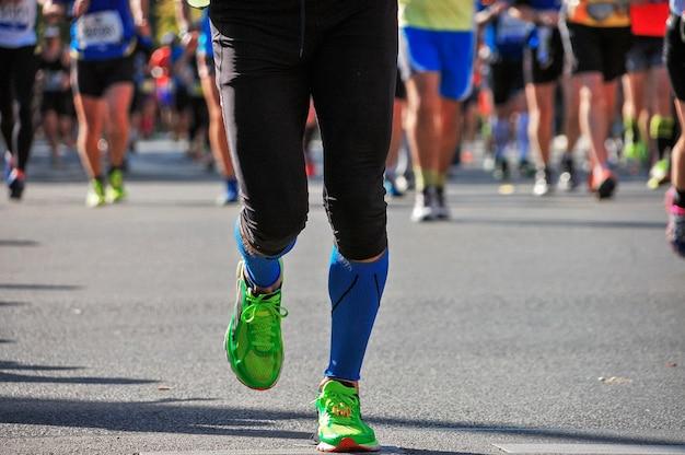 Maratona di corsa, piedi di molti corridori su strada, competizione sportiva, fitness e concetto di stile di vita sano