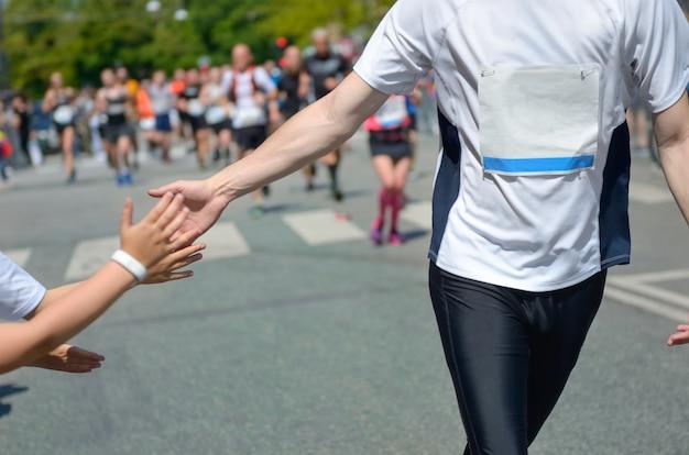 Gara podistica maratona, supporto corridori su gara su strada, mano del bambino che dà il cinque, atleti che supportano il bambino che corre, concetto di sport