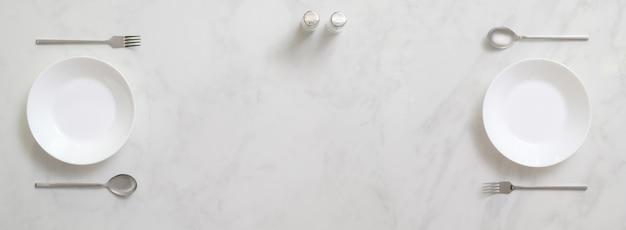 Tavolo da pranzo in marmo con due set di piatto bianco e argenteria, bottiglie di condimento e spazio di copia