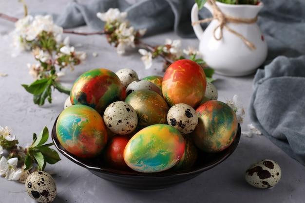 Uova di pasqua in marmo dipinte con colori alimentari multicolori e uova di quaglia in un piatto su una superficie grigia