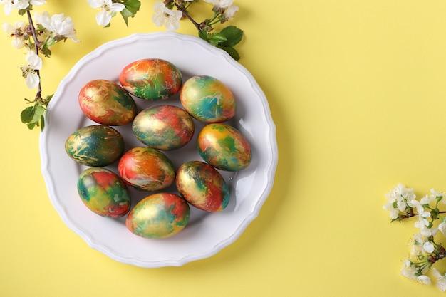 Uova in marmo dipinte con coloranti alimentari per pasqua localizzate su un piatto bianco su sfondo giallo. vista dall'alto. spazio per il testo