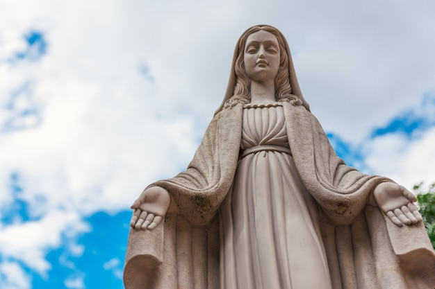Figura in marmo della vergine maria. sfondo azzurro del cielo.