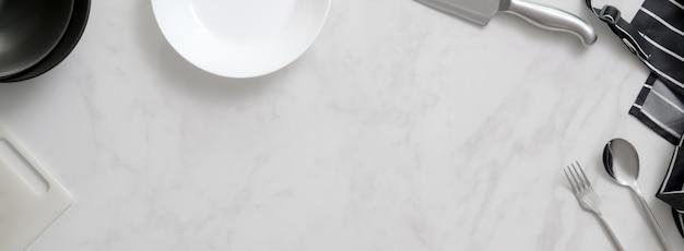 Bancone da cucina in marmo con utensili da cucina, argenteria, grembiule, coltello d'argento, tagliere e spazio copia