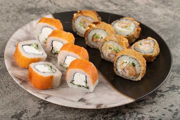 Piatto di marmo di philadelphia e rotoli di sushi caldi sul tavolo di pietra.