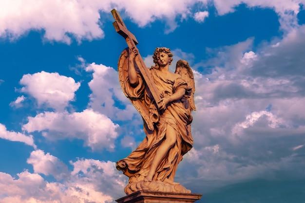 Statua in marmo di angelo con la croce al tramonto, uno dei dieci angeli sul ponte sant'angelo, simboli della passione di cristo, roma, italia