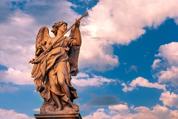 Statua in marmo di angelo con la lancia al tramonto, uno dei dieci angeli sul ponte sant'angelo, simboli della passione di cristo, roma, italia