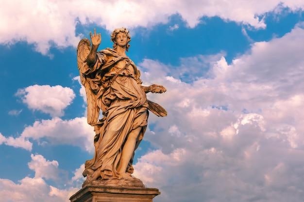 Statua in marmo di angelo con i chiodi al tramonto, uno dei dieci angeli sul ponte sant'angelo, simboli della passione di cristo, roma, italia
