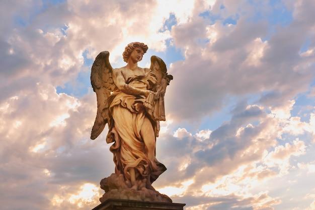 Statua in marmo di angelo con le fruste al tramonto, uno dei dieci angeli sul ponte sant'angelo, simboli della passione di cristo, roma, italia