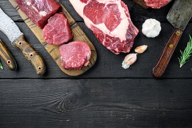 Set di taglio di bistecca di carne di manzo marmorizzata, tomahawk, t bone, club steak, rib eye e tagli di filetto, su sfondo di legno nero, vista dall'alto piatta, con spazio di copia per il testo