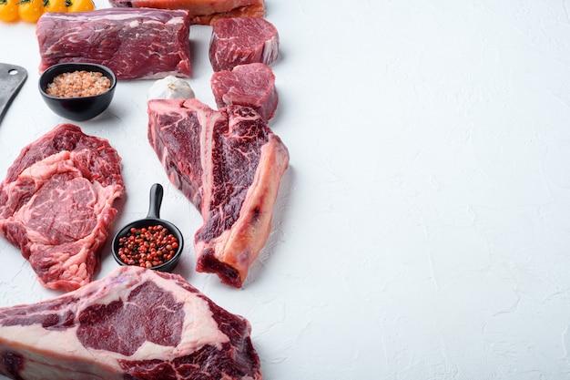 Set di taglio di bistecca di carne di manzo marmorizzata, tomahawk, t bone, club steak, rib eye e tagli di filetto, su pietra bianca