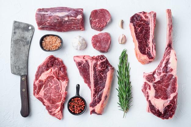 Bistecca di carne di manzo marmorizzata tagliata, tomahawk, t bone, bistecca club, costata e tagli di filetto, su pietra bianca