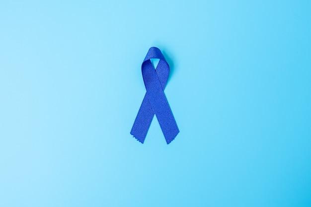 Marzo mese della consapevolezza del cancro del colon-retto, nastro di colore blu scuro per sostenere le persone che vivono e le malattie. sanità, speranza e concetto di giornata mondiale del cancro