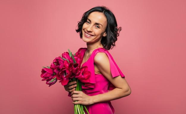 Regali di marzo. foto ravvicinata di una splendida donna in un abito rosa brillante, che guarda nell'obiettivo con un ampio sorriso, con in mano un mazzo di fiori primaverili.