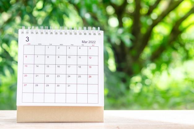 Mese di marzo, scrivania del calendario 2022 per l'organizzatore per la pianificazione e il promemoria sul tavolo di legno con sfondo verde della natura.