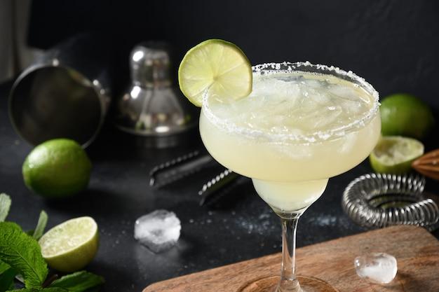 Margarita cocktail guarnire lime e cubetto di ghiaccio su sfondo nero
