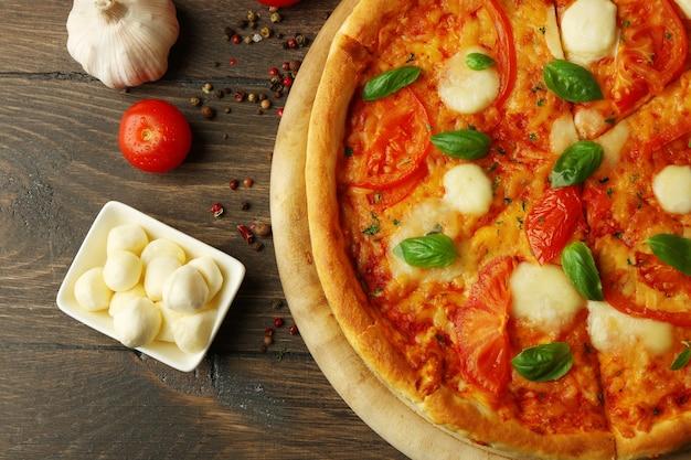 Pizza margherita con pomodori, aglio, spezie e mozzarella su tavola di legno