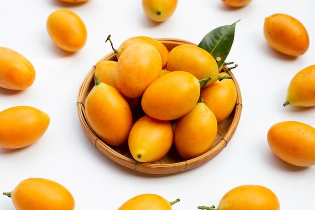 Frutta della prugna mariana isolata sulla superficie bianca