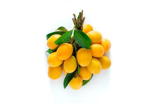 Prugna mariana o ma yong chid (in thailandese) che sembra prugna ma sa di mango su sfondo bianco.