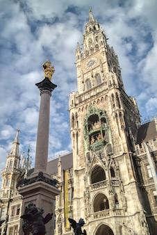 Marienplatz è una piazza centrale con la colonna di santa maria e il nuovo municipio su uno sfondo di cielo nuvoloso blu, monaco di baviera, baviera, germania.