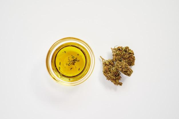 I germogli di marijuana e una piccola ciotola di olio di cbd su uno sfondo bianco